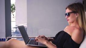 De zitting van de Freelancervrouw op een lanterfanter dichtbij de pool en het werken aan laptop, langzame motie stock videobeelden