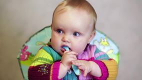 De zitting van het babymeisje als kinderen` s voorzitter en het spelen met een lepel in de ruimte stock videobeelden