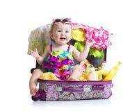 De zitting van het babymeisje in boomstam met dingen voor stock fotografie