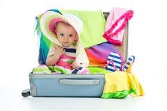 De zitting van het babymeisje in boomstam met dingen voor geïsoleerde vakantiereis stock afbeeldingen