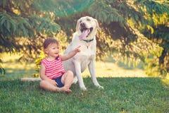 De zitting van het babymeisje met buiten hond in park royalty-vrije stock foto