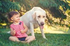 De zitting van het babymeisje met buiten hond in park royalty-vrije stock afbeelding