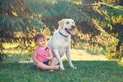 De zitting van het babymeisje met buiten hond in park royalty-vrije stock fotografie