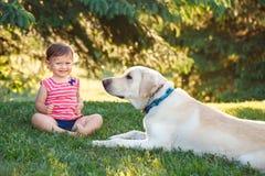 De zitting van het babymeisje met buiten hond in park stock fotografie