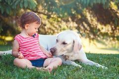 De zitting van het babymeisje met buiten hond in park royalty-vrije stock afbeeldingen