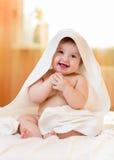 De zitting van het babymeisje onder een handdoek met een kap na bad Stock Foto