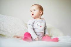 De zitting van het babymeisje op bed royalty-vrije stock foto's