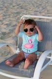 De zitting van het babymeisje op een ligstoel Royalty-vrije Stock Foto's