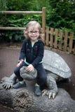 De zitting van het babymeisje op een schildpad Stock Foto's