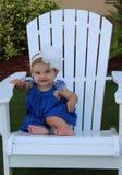 De zitting van het babymeisje op een stoel Stock Afbeeldingen