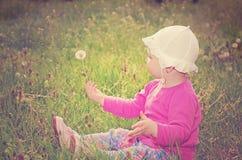 De zitting van het babymeisje op groen gras Stock Foto's