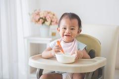 De zitting van het babymeisje op hoge stoel en voedt zelf haar Royalty-vrije Stock Foto's