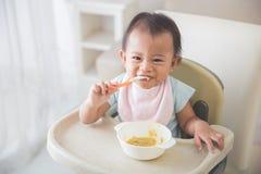 De zitting van het babymeisje op hoge stoel en voedt zelf haar Stock Foto's