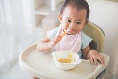 De zitting van het babymeisje op hoge stoel en voedt zelf haar Royalty-vrije Stock Fotografie