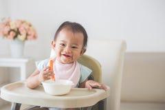 De zitting van het babymeisje op hoge stoel en voedt zelf haar Stock Fotografie