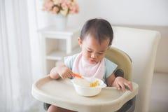 De zitting van het babymeisje op hoge stoel en voedt zelf haar Royalty-vrije Stock Afbeeldingen