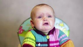 De zitting van het babymeisje op kinderen` s stoel in het huis en het schreeuwen stock video
