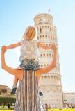 De zitting van het babymeisje op moedersschouders in Pisa Stock Afbeelding