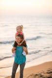 De zitting van het babymeisje op schouders van moeder op strand Royalty-vrije Stock Afbeeldingen