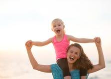 De zitting van het babymeisje op schouders van moeder op strand Stock Foto's