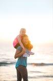 De zitting van het babymeisje op schouders van moeder op strand Royalty-vrije Stock Afbeelding