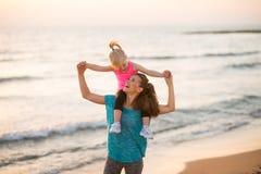 De zitting van het babymeisje op schouders van moeder op strand stock afbeeldingen