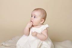 De Zitting van het babymeisje op Tandjes krijgen Stock Foto's