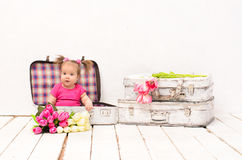 De zitting van het babymeisje in oude uitstekende koffers Stock Fotografie