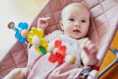 De zitting van het babymeisje in uitsmijter en het spelen met kleurrijk speelgoed stock foto's