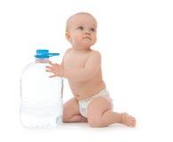 De zitting van het de babymeisje van het zuigelingskind met grote fles drinkwater Stock Foto