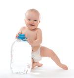 De zitting van het de babymeisje van het zuigelingskind met grote fles drinkwater Stock Foto's