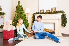 De zitting van het de liefdepaar van Nice op tapijt dichtbij de open haard Vrouw en man het vieren Kerstmis stock afbeelding