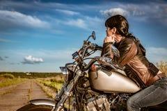 De zitting van het fietsermeisje op motorfiets stock foto's