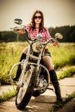 De zitting van het fietsermeisje op motorfiets royalty-vrije stock foto's