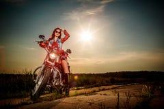 De zitting van het fietsermeisje op motorfiets stock foto