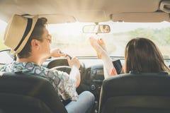 De zitting van het Hipsterpaar in auto en het genieten van staaf van reis stock foto