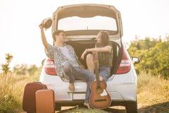De zitting van het Hipsterpaar bij de rand van de autoboomstam in aard De reisconcept van de toerismeweg royalty-vrije stock afbeeldingen