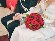 De zitting van het huwelijkspaar in de kerk hand in hand met de bruid die een boeket van rode rozen houden royalty-vrije stock foto's