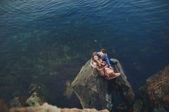 De zitting van het huwelijkspaar op grote steen rond blauwe overzees stock foto's