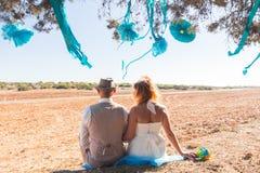 De zitting van het jonggehuwdepaar onder schaduw van boom in de zomer Royalty-vrije Stock Afbeelding