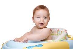 De zitting van het kind in babystoel en glimlach. Stock Afbeelding