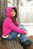 De zitting van het kind onder boom in de winter Royalty-vrije Stock Foto