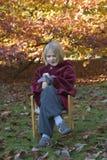 De zitting van het kind op een stoel in het park Stock Afbeelding