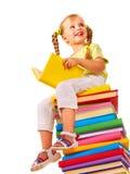 De zitting van het kind op stapel boeken. stock foto