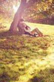De zitting van het liefdepaar onder een boom in het kleurrijke de herfstbos Stock Afbeelding