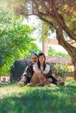 De zitting van het liefdepaar op het gras in het park stock foto's