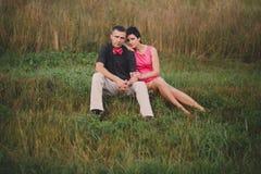 De zitting van het liefdepaar op het gras Stock Foto