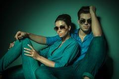 De zitting van het manierpaar op studioachtergrond Stock Fotografie