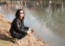 Het meisje en de rivier van de zitting Stock Foto's