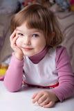 De zitting van het meisje bij de lijst Royalty-vrije Stock Fotografie